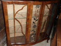 It has a serpentine (curvy) front, 2 glass insert doors