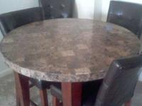 Brown marbletop table with four chairs. Table and two