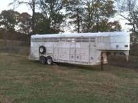 32ft gooseneck stock trailer with seven exterior doors.