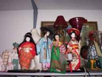 a collection of geisha dolls. the dolls on each end are