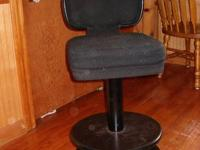 Four black fabric padded bar stools with backs. Seat is