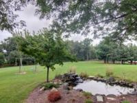 Nature abounds this 5.2 acre private estate. Stroll in