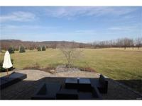 Setting on a level lot overlooking a pond in Saddle