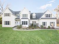 This young, sun-filled center hall Colonial is ideally