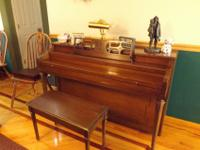 A very nice dark wood spinnet piano made by Hallet and