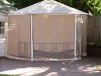 Aluminum framed screened gazebo with canvas top cover.