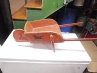 This is a child's size antique wooden wheelbarrow.