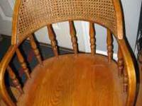 Solid oak desk chair with rattan back. Large casters.