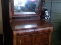 Brown, antique dresser with mirror and wheels. Locks on