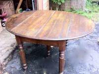 This lovely dark-brown-stained antique table easily