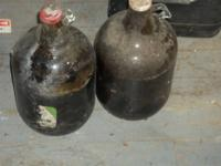 ANTIQUE GALLON JUGS WITH ORIGINAL LIDS.