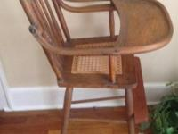 This antique high chair is made of oak with a woven
