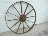 This is a vintage all metal wagon wheel in rustic