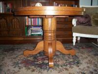 """Antique oak pedestal table. 42"""" diameter on casters."""