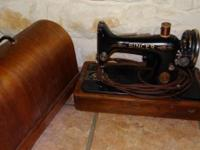 Antique black sewing machine with gold trim and a