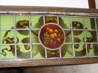 This antique Stained Glass Window is in a wood frame.