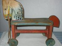 This antique wood riding horse was made in the USA by
