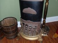 Antique oval cast iron and metal gas heating stove, has
