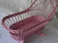 Antique pink wicker rocking doll cradle for sale.