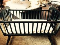 A very good bassinet - wood finish - with wheels and