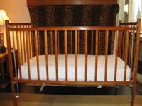 Great looking wooden crib. New mattress cover.