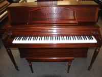 This is a handsome Baldwin console piano, in red