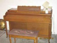 Baldwin upright piano with its bench and a nice lamp.