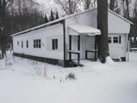 This mobile home is located right between Higgins Lake