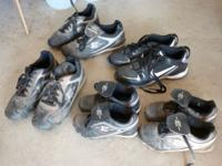 Several pair of baseball, softball and football cleats