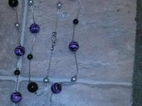 Purple beaded necklace rests just beneath chest level.