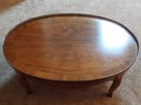 Beautiful oval walnut coffee table made by Baker.  It's