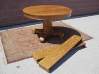"""A fine antique 48"""" round tiger oak dining table with 2"""