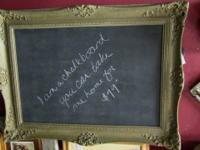 Large chalkboard in an ornate frame. Measures