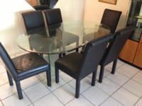 Glass dining room table with six chairs for sale. The