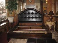 Beautiful modern king bed with black leather headboard.