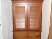This beautiful armoire serves as a TV cabinet with