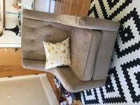 Beige winged arm chair. Button tufting, plush cushion,