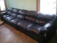 long couch. It's black leather with a little damage.