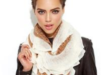 Layers of flirty ruffles give this open knit scarf a