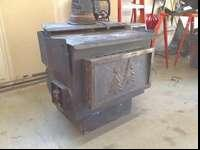 Large wood burning stove. Has two fans ducted behind