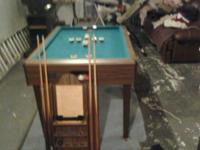 Billiard table in excellent shape with cues and rack.