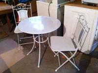 Round metal bistro table and folding chairs. Two sets