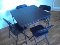 Black Card Table with four cushioned seats. Has two