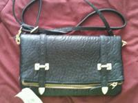 Black crossbody bag with gold buckle information.