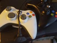 Black xbox 360 (slim) with two wireless controllers