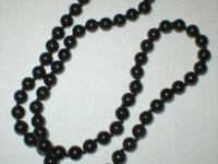 "This black beaded necklace hangs 11 1/2"" long. It is in"