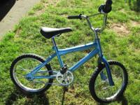 A painted blue young kid's bike that seems to be in