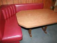 Corner booth with table, seat is upholstered in a