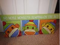Bright, colorful sock monkey wall hangings and green