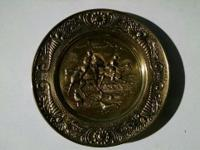 This mid-century brass repouss decorative hanging plate